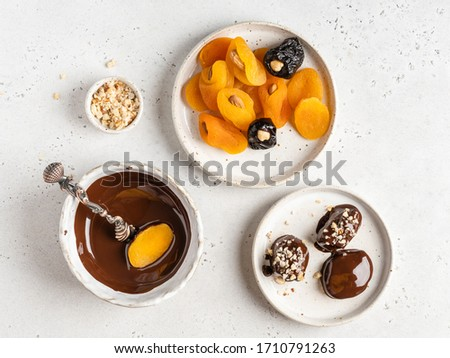 Step by step cooking. Raw and healthy candies. Dried fruits and nuts in dark chocolate. Top view, white background. Chocolate covered dried apricots and prunes stuffed with cashew and almond nuts. Foto stock ©