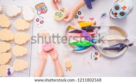 Step by step. Flat lay. Mother and daughter decorating sugar skull cookies with royal icing for Dia de los Muertos holiday.