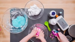 Step by step. Flat lay. Mother and daughter making colorful fluffy slime.