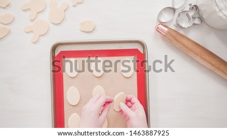 Step by step. Flat lay. Unbaked Easter sugar cookies arranged for baking on a baking sheet. #1463887925