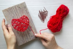 Step by step instruction: DIY gift for Valentine's Day. step 3: hands are tying red threads on nails in the heart-shaped painting. red threads and nails are lying nearby