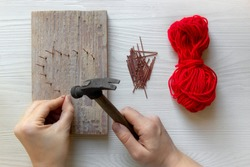 Step by step instruction: DIY gift for Valentine's Day. step 2: hands hammer nails into a wooden board in the form of a heart. red threads and nails lie nearby.