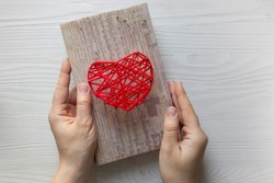 Step by step instruction: DIY gift for Valentine's Day. step 4: hands hold the finished pano picture with a heart made of threads and nails on a wooden board