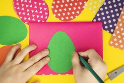 Step-by-step instructions for creating an Easter egg toy. The DO-IT-YOURSELF concept. The boy outlines the outline of a green paper egg for further cutting it out
