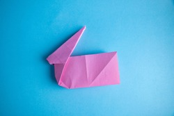 Step-by-step instructions for creating an origami bunny out of colored paper on a blue background, for a decorative Easter party decoration or for small Easter gifts.