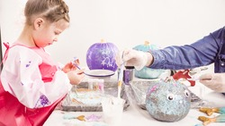 Step by step. Mother and daughter decorating art pumpkins with glitter in mermaid theme for Halloween.