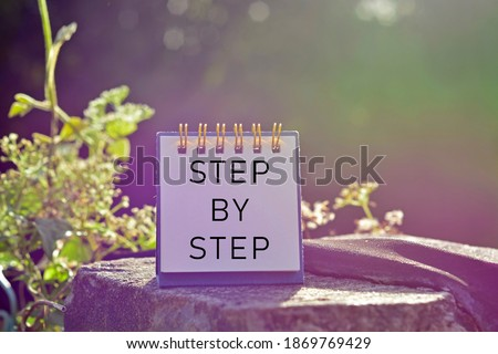 Photo of  Step by step text written on white note with blurred background of hanging bridge - Powerful words