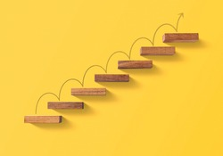 Step by step to grow your business, business success or career path success concept. Wooden blocks arranged in a shape of staircase on yellow background.
