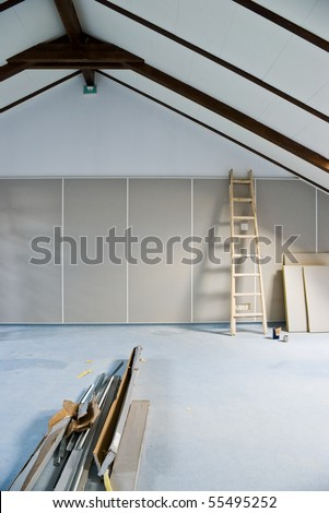 step ladder and construction materials in empty attic room