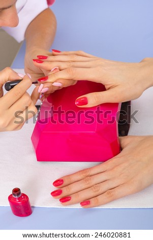 step of manicure process: nail covering with nail gel polish