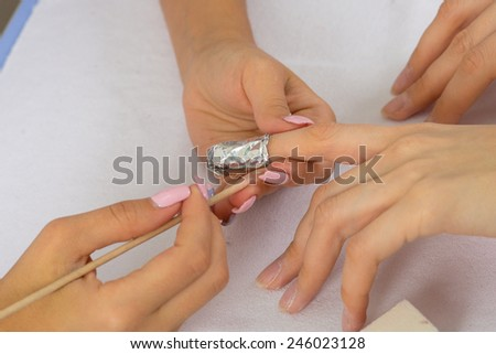 step of manicure process: nail gel polish removal using foil pieces