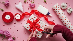Step 12.Step-by-step instructions for wrapping gifts for Valentine's Day. Woman wraps a gift with wrapping white paper in heart and seals the edges with glue on a pink background top view, flat lay.