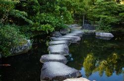 Step stones path over a pond in Koko-en Garden near White Egret Castle, in Himeji, Hyogo Prefecture in Japan