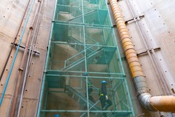Step zigzag staircase safety with net fall-protection in underground construction site or fire escape, a ladder or stairs outside a building that allow people in the building to escape a fire.