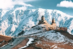 Stepantsminda, Gergeti, Georgia. Famous Gergeti Trinity Tsminda Sameba Church In Early Winter Landscape. Suv Moving Near Church In Beautiful Georgian Landscape In Early Winter