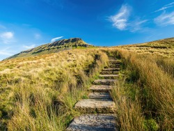 Steps climbing up towards the mountain of Pen-y-ghent in the Yorkshire Dales National Park. The mountain is 2,277 feet high.