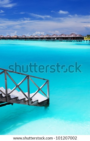 Steps into amazing blue lagoon with over-water bungalows