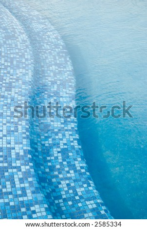 steps into the blue pool at the tropical resort. Vertical orientation