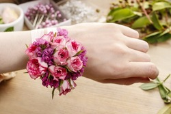 Steps of making wrist corsage. Florist at work. Woman making beautiful bouquet of pink roses.