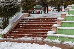 Steps of the stairs, trees and bushes in the park in snowy weather. Selective focus.