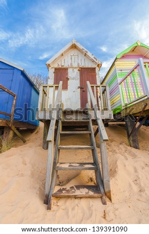 steps up to a weathered beach hut on golden sand
