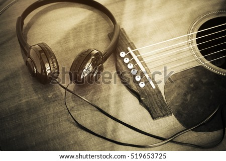 Stereo headphones with guitar,home folk song recording concept , processed in vintage style.