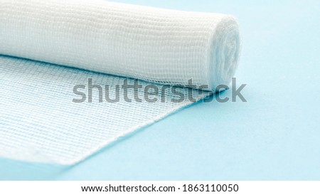 Sterile bandage on a blue background. White medical cotton bandage on a blue background. First aid - a white unfolded gauze bandage. White cotton bandage isolated on blue background. Stock photo ©