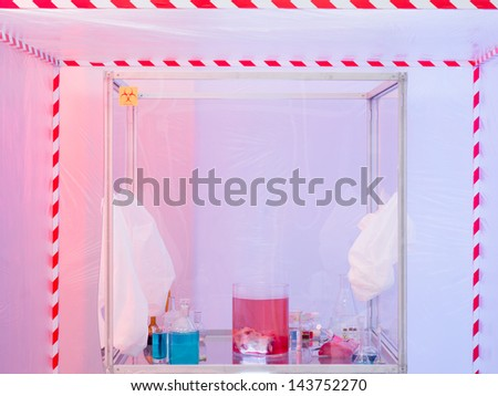 sterile chamber in containment tent with experiment glassware with colored liquid substances and raw meat