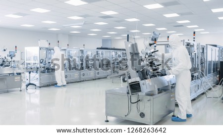 Sterile High Precision Manufacturing Laboratory where Scientists in Protective Coverall's Turn on Machninery, Use Computers and Microscopes, doing Pharmaceutics, Biotechnology Semiconductor Research.