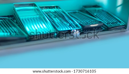 Sterilization of dental instrument with ultraviolet lamp in clinic. Copyspace, place for text. Various medical instruments and accessories inside an UV-sterilizer. instruments sterilized by UV