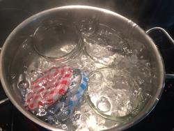 Sterilizing glass jars in a steel pan; steaming bubbling wather