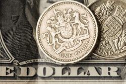 Sterling pound coin on an American one dollar bill.