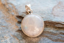 Sterling silver pendant with mineral moon stone gemstone on rocky background