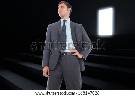 Stern businessman with hand on hip against steps leading to light in the darkness
