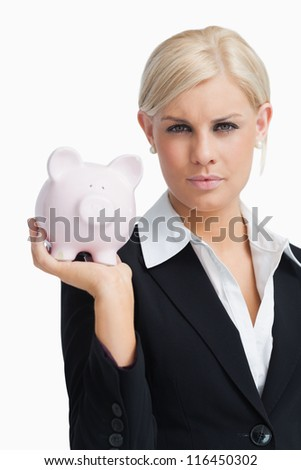 Stern businesswoman holding a piggy-bank against white background