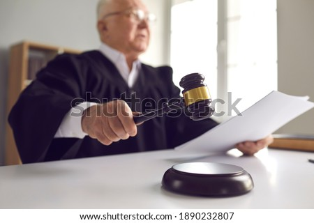 Stern judge with paper document pronouncing sentence in a court of law. Judge finds the accused guilty, passes judgement and rules case closed. Hand holding gavel and hitting sound block in close-up Foto d'archivio ©