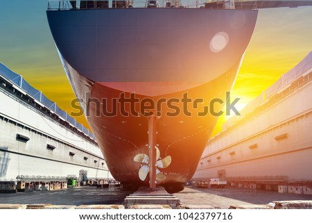Stern ship propeller big cargo ship under the Overhauled in floating dry dock in shipyard thailand on sunset background