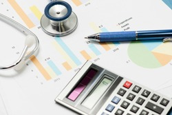 Stethescope, pen and calculator with financial charts and reports to illustrate medical business concept.