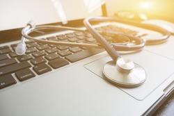 Stethoscope,a medical instrument for listening to action of  heart or breathing lay on laptop keyboard in hospital office,Medical concept ,relax time doctor,selective focus,vintage color.morning light