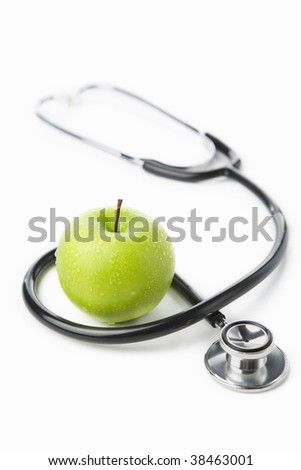 Stethoscope and a green apple over white for health lifestyle concept