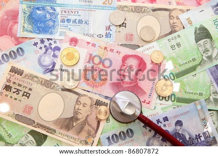 stethoscope and Background of asian currency (include Korean Won, Taiwan dollar, Chinese Money yuan , Hong Kong Dollar, japanese Yen)