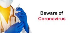 Stethoscope and doctor hands holding syringe with text BEWARE OF CORONAVIRUS on white background. Covid-19 concept