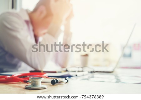 Stethoscope and doctor sitting with laptop stress headache about work in hospital