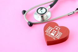 Stethoscope and heart object with hospital pictogram on pink background