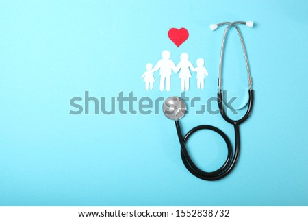 stethoscope and heart on a colored background top view. Family medicine