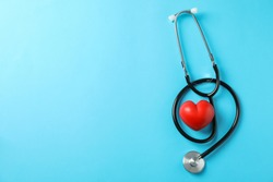 Stethoscope and heart on blue background, space for text. Healthcare