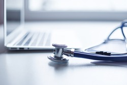 Stethoscope and laptop on doctor working desk with blurred focus for background, business and health care concept