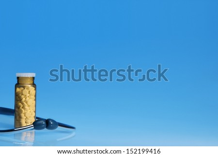 Stethoscope and medicine bottle with pills on blue, reflective background  #152199416