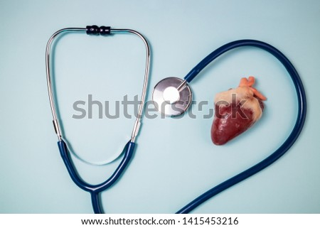 Stethoscope and raw heart on blue background. Medical background. Medicine, medical examination, health care heart protect and cardiology concept. Top view #1415453216