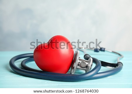 Stethoscope and red heart on wooden table. Cardiology concept #1268764030